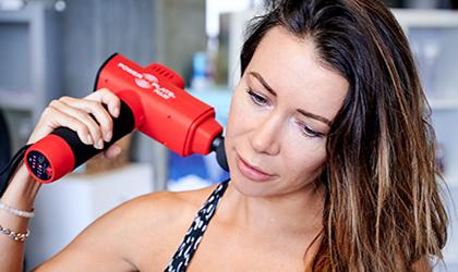 lady using massage gun on neck